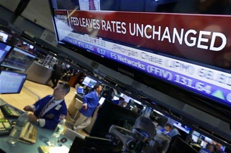 A television screen on the floor of the New York Stock Exchange shows the decision of the Federal Reserve, Wednesday, July 29, 2015. AP