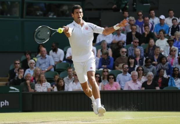 Novak Djokovic of Serbia hits a shot during his match against Marin Cilic of Croatia at the Wimbledon Tennis Championships in London, July 8, 2015.   REUTERS/Suzanne Plunkett -