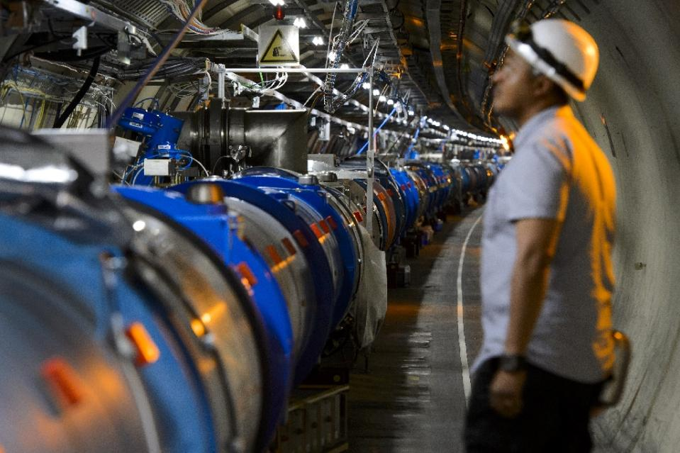 A scientist looks at a section of the European Organisation for Nuclear Research Large Hadron Collider, during maintenance works in Meyrin, near Geneva on July 19, 2013. Photo: AFP/File