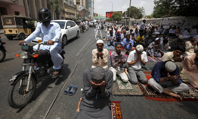 Vehicles move past men offering their Friday prayers near a mosque during the holy month of Ramadan in Karachi, Pakistan, July 3, 2015. REUTERS/Akhtar Soomro