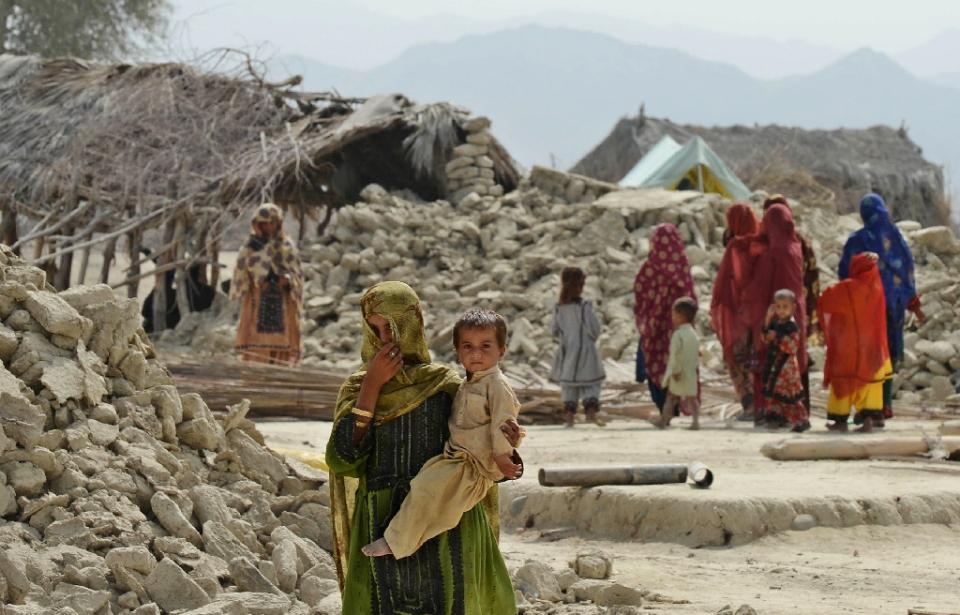 File- Pakistani earthquake survivors walk next to their destroyed houses in Peerander in 2013. Photo: AFP