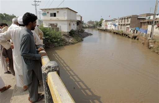 Pakistani villagers watch a stream over flowing due to rain in Peshawar, Pakistan, Friday, July 24, 2015. Pakistani authorities say flash floods, triggered by monsoon rains, have killed 12 more people across the country, bringing the overall death toll since early last week to 15, as rescuers struggle to move those stranded to safer places. (AP Photo/Mohammad Sajjad)