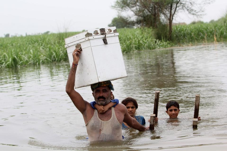 Pakistani villagers wade through floodwaters in the Layyah district of Punjab province on July 23, 2015. Photo: AFP