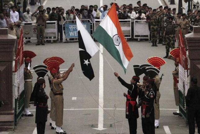 Pakistani rangers (wearing black uniforms) and Indian Border Security Force (BSF) officers lower their national flags during a daily parade at the Pakistan-India joint check-post at Wagah border, near Lahore November 3, 2014.  Photo: Reuters