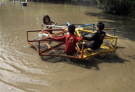 Pakistani children take a ride on a roundabout at a flooded park caused by heavy rains in Lahore, Pakistan, Tuesday, July 21, 2015. A Pakistani local government spokesman said this week's flash floods triggered by monsoon rains in the country's north have killed at least two people and damaged several homes, roads and bridges. AP