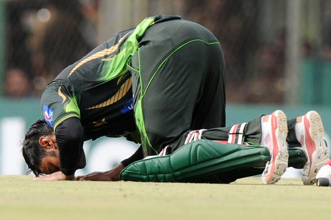 Pakistan cricketer Mohammad Hafeez touches the ground after he scored a century (100 runs) during the first One Day International (ODI) match between Sri Lanka and Pakistan at the Rangiri Dambulla International Cricket stadium in Dambulla, some 150 kms north of Colombo on July 11, 2015. Photo: AFP