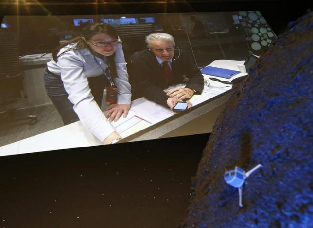 Paolo Ferri (R) Head of Rosetta Mission Operations, seen on a video projection behind a model of the Philae lander, reacts after the successful landing of the lander on comet 67P/ Churyumov-Gerasimenko, at the European Space Agency's (ESA) headquarters in Darmstadt November 12, 2014.    REUTERS/Ralph Orlowski/Files