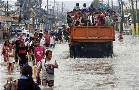 Flood victims are evacuated on a truck while other residents wade through floodwaters on a street in Bacoor, Cavite near Manila, August 20, 2013. REUTERS/Erik De Castro