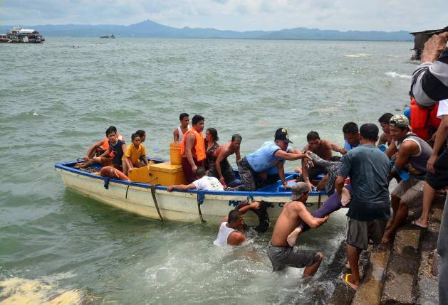 A body is carried by rescuers during a search and rescue operation following a ferry capsize in Ormoc city, central Philippines July 2, 2015. REUTERS/Ronald Frank Dejon
