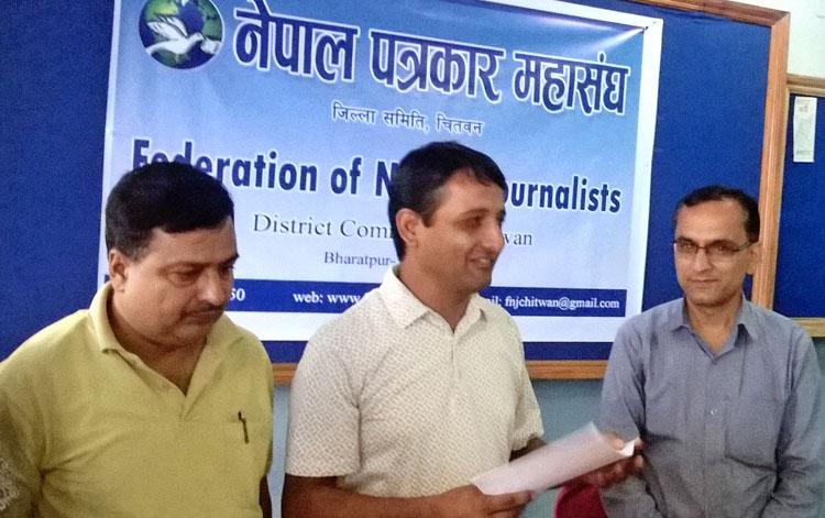 FNJ Chitwan President Hari Prasad Pokharel (centre) handing over feedback on the draft of the constitution to Chitwan Constituency-3 lawmaker Krishna Bhakta Pokharel (right) in Chitwan on Sunday, July 19, 2015.