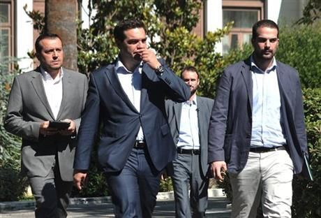 Greece's Prime Minister Alexis Tsipras, center, leaves after a meeting with Greek political party leaders at the Presidential Palace as Minister of State Nikos Pappas, left, and Government spokesman Gabriel Sakellaridis, right, follow him in Athens, Monday, July 6, 2015. AP