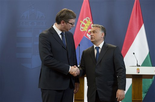 Serbian Prime Minister Aleksandar Vucic, left, and his Hungarian counterpart Viktor Orban, right, shake hands after a joint press conference in the Parliament building in Budapest, Wednesday, July 1, 2015. Vucic is on a one-day official visit to Hungary. (Szilard Koszticsak/MTI via AP)