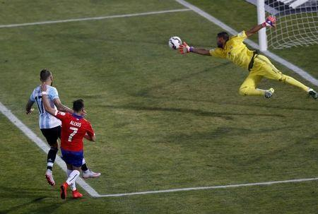Argentina's goalie Sergio Romero lunges to stop a shot by Chile's Alexis Sanchez (7) as Argentina's Nicolas Otamendi looks on during their Copa America 2015 final soccer match at the National Stadium in Santiago, Chile, July 4, 2015.  Photo: Reuters