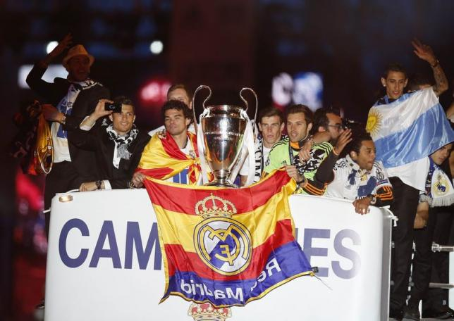 Real Madrid players celebrate on top of an open bus as they arrive at the Cibeles square after winning their Champions League final soccer match against Atletico Madrid, in Madrid May 25, 2014. REUTERS/Andrea Comas