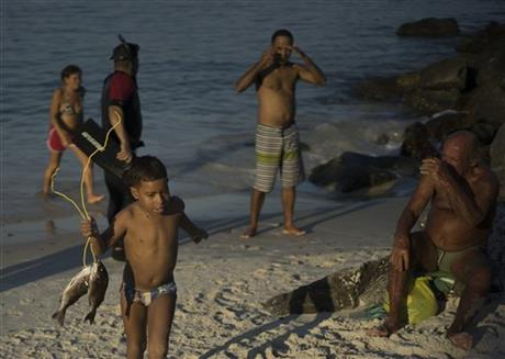 In this July 12, 2015 photo, a boy walks with his father's catch of the day from the Marina da Gloria, in Rio de Janeiro, Brazil. AP