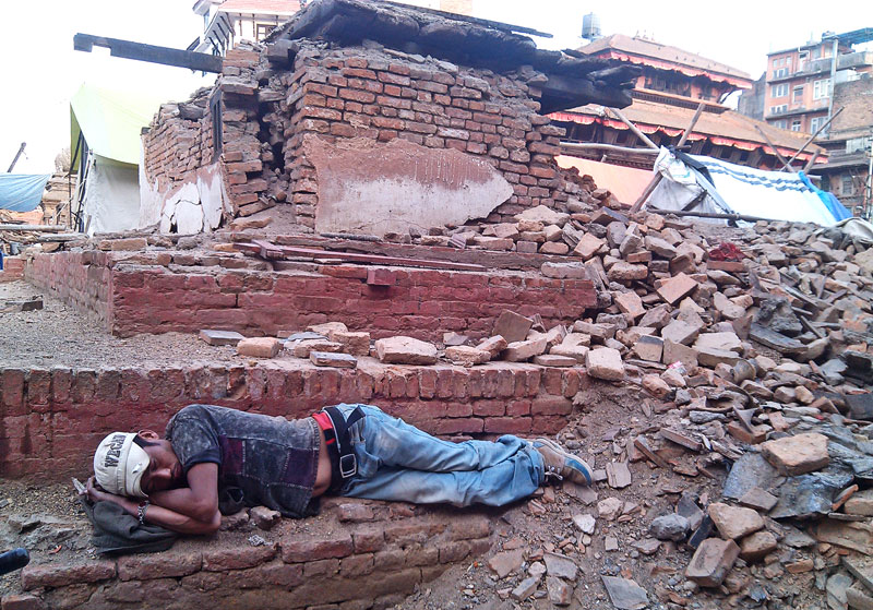 A man sleeps on the western side of the ruins of iconic Kashthamandap. Kathmandu got its name from the wooden monument that collapsed in the devastating earthquake on April 25, 2015.nKashthamandap now remains in memory (and pictures) only. Should be reconstructed! Photo: instagram.com/kashthamandap