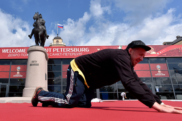A worker prepares the red carpet close to the Constantine (Konstantinovsky) Palace in St nPetersburg on Friday, on the eve of the Preliminary draw for the 2018 FIFA World Cup. Photo: AFP
