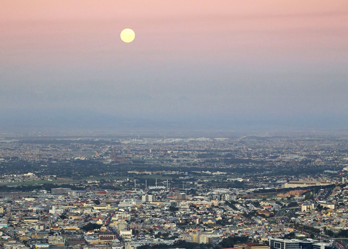 The moon rises over the city as it enjoys a respite from stormy winter weather in central Cape Town, South Africa, July 1, 2015. REUTERS/Mike Hutchings