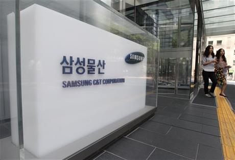 Office workers walk by a logo of Samsung C&T Corporation at its head office in Seoul, South Korea, Wednesday, July 1, 2015. Photo: AP
