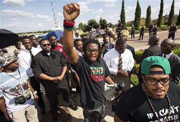 Malik Muhammad raises his fist during a demonstration calling for the firing and indictment of Texas State Trooper Brian Encinia, Sunday, July 26, 2015, in Katy, Texas. Sandra Bland was found dead in her cell on July 13 in the Waller County Jail, just days after being arrested by Encinia during a traffic stop. Authorities determined through an autopsy that Bland hanged herself with a plastic bag. Photo: Sandra Bland