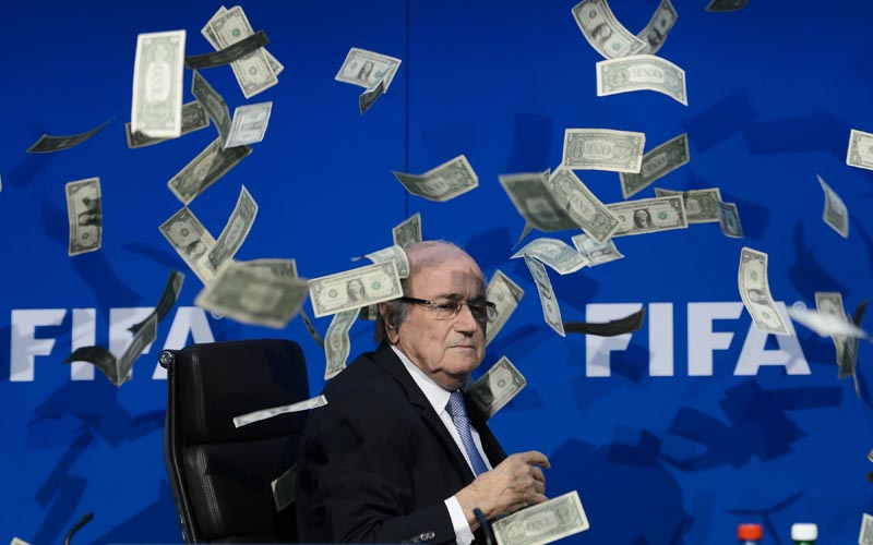 FIFA president Sepp Blatter looks on with fake dollars note flying around him thrown by a protester during a press conference at the football's world body headquarter in Zurich on Monday. Photo: AFP