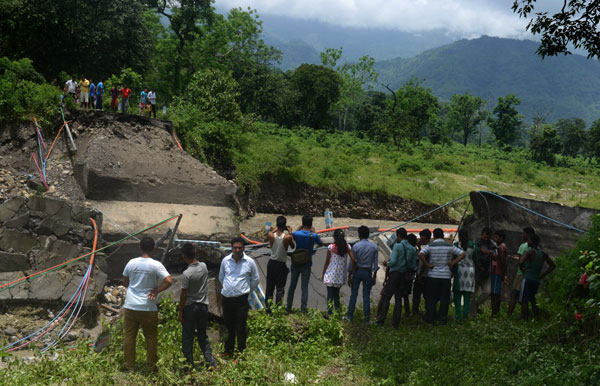 Indian bystanders look at a damaged bridge in the village of Garidhura some 35kms from Siliguri on July 1, 2015, after landslides struck the eastern state of West Bengal. Landslides triggered by heavy rain have killed at least 11 people across India's famed tea-growing region of Darjeeling, with more feared trapped under mounds of mud and debris, police said. AFP