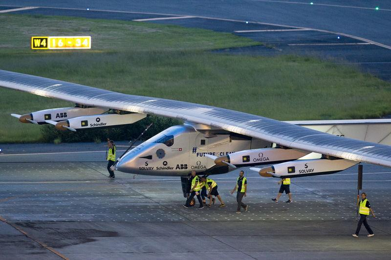 Crew members push the solar-powered plane Solar Impulse 2 to its parking position at Nagoya airport after changing weather conditions thwarted a planned take-off, June 24, 2015.  Photo: Reuters