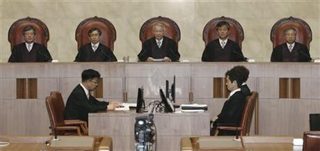 South Korean Supreme Court Chief Justice Yang Sung-tae, top center, sits with other judges before the judgment at the Supreme Court in Seoul, South Korea, Thursday, July 16, 2015.  AP