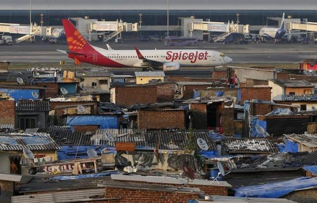 A SpiceJet passenger aircraft taxis on the runway at the airport next to a slum area in Mumbai December 19, 2014.  Photo: Reuters