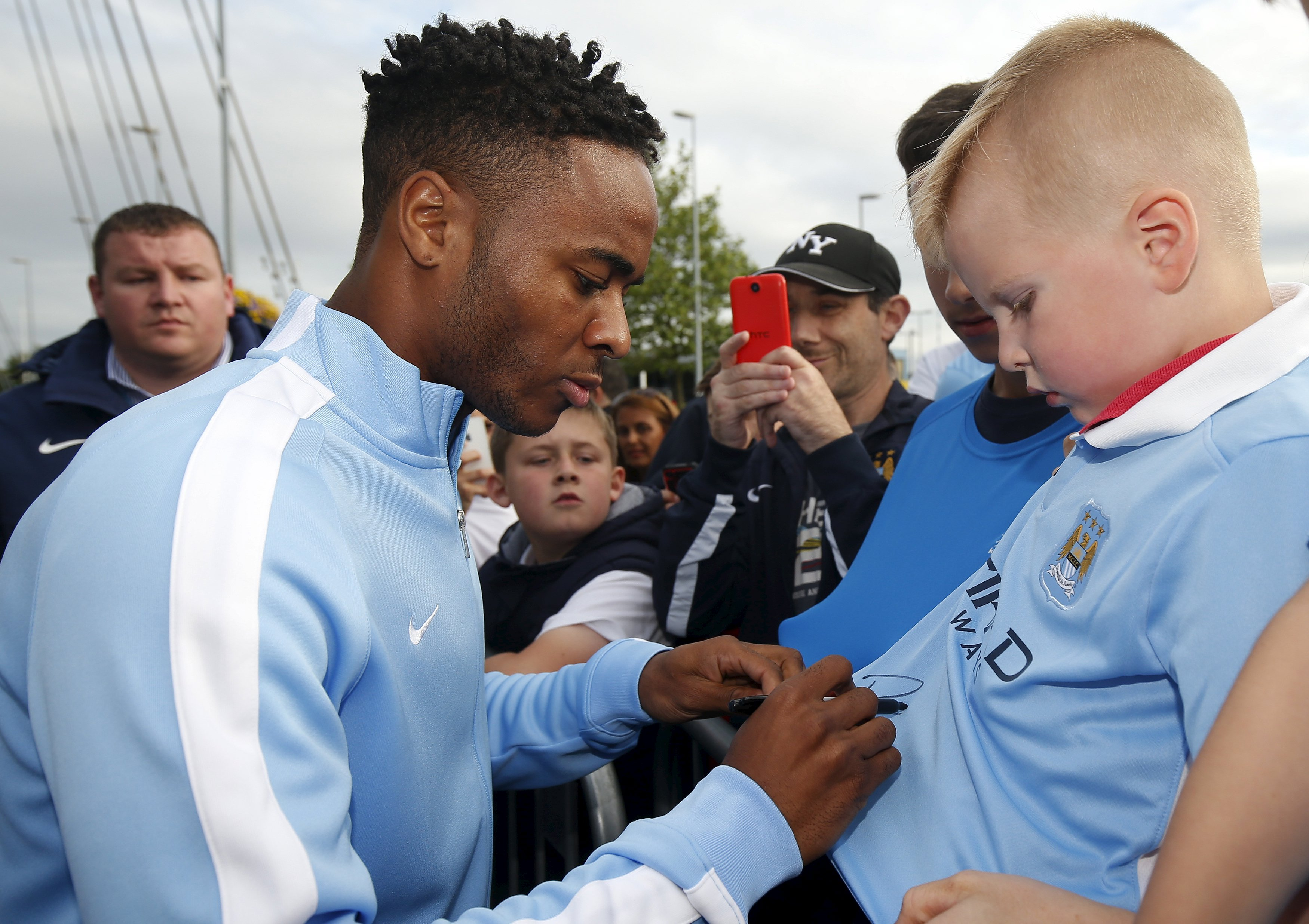 Manchester Cityu2019s new player Raheem Sterling signing autographs for supporters as he leaves the club's Etihad Stadium in Manchester on Wednesday. Photo: Reuters