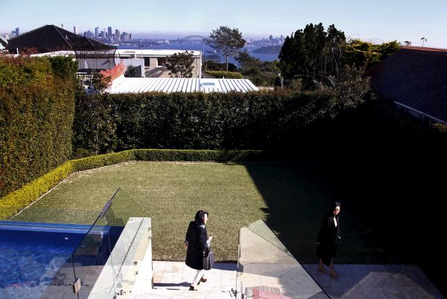 The Sydney Opera House and Harbour Bridge can be seen behind real estate agent LuLu Sun (R) as she escorts Bao Fang, a potential buyer from Shanghai, during an inspection of a property for sale in the Sydney suburb of Vaucluse, Australia, July 11, 2015. REUTERS/David Gray