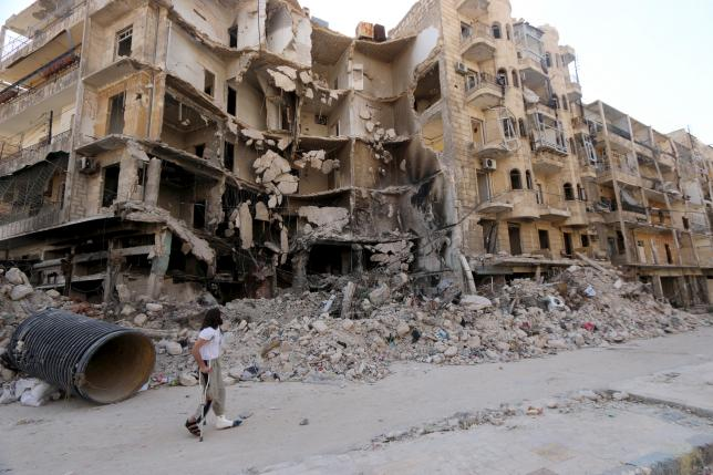 A man walks with the aid of a crutch past damaged buildings in the old city of Aleppo June 27, 2015. REUTERS/Abdalrhman Ismail