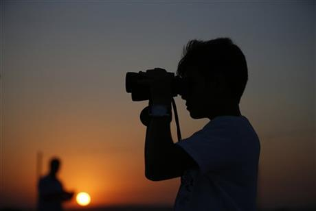 A youth uses binoculars to look at Turkish army tanks holding positions, near the border with Syria, in the outskirts of the village of Elbeyi, east of the town of Kilis, in southeastern Turkey, Thursday, July 23, 2015. AP