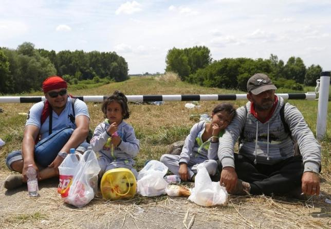 Migrants from Syria sit after they crossed the border from Serbia to Hungary, walking on the dam near the Tisza river near the city of Szeged, Hungary, on June 29. REUTERS/Laszlo Balogh