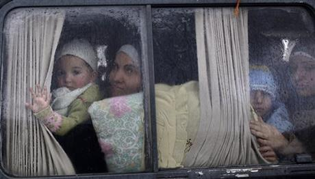 FILE - In this Dec. 20, 2012, file photo, Syrian refugees, who fled their home in Idlib due to a government airstrike, look out of a vehicle's window just after crossing the border from Syria to Turkey in Cilvegozu, Turkey. AP