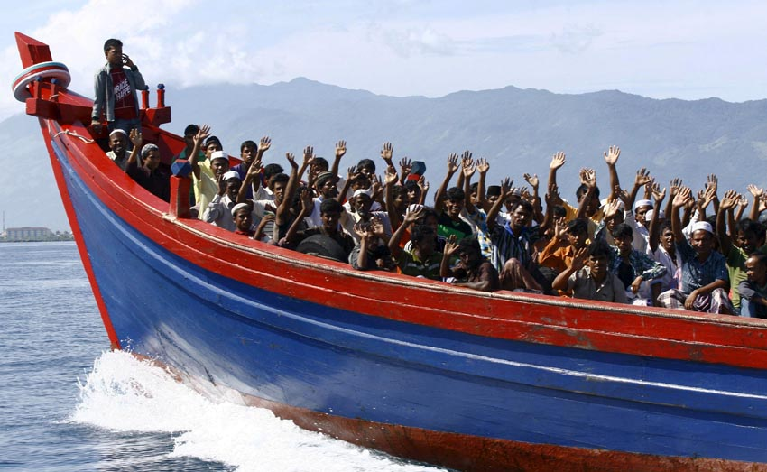 Ethnic Rohingya refugees from Myanmar wave as they are transported by a wooden boat to a temporary shelter in Krueng Raya in Aceh Besar in this April 8, 2013. Photo: Reuters/File