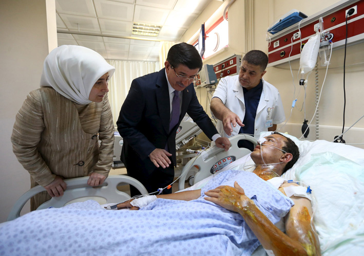 Turkey's Prime Minister Ahmet Davutoglu (2nd L), accompanied by his wife Sare Davutoglu, visits a survivor who was wounded in Monday's bomb attack in Suruc, in Sanliurfa, Turkey, July 21, 2015. Photo: Reuters