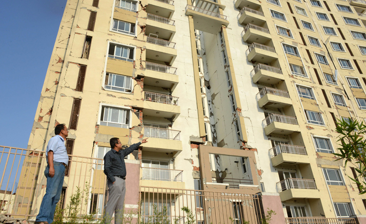 This photograph taken on June 14, 2015, shows vice-president of the owners committee Deepak Rajbhandary (left) looking on as a resident points to damage on the structure of The Park View Horizon Apartment building in Kathmandu.   Residents are taking some persuading to move back into Kathmandu's 17-storey Park View Horizon apartment block after a 7.8 magnitude quake in April 2015, killed more than 8,800 people and destroyed nearly half a million buildings in Nepal, a country where high-rise buildings are still something of a rarity and are limited to Kathmandu. Photo: AFP
