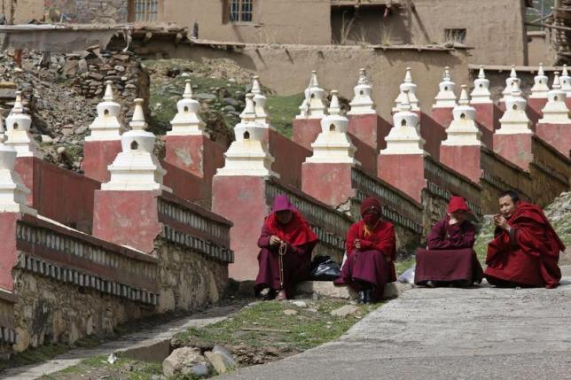 File- Tibetan monks sit at an entrance to the Dzamthang Jonang monastery, where Tibetan woman Kalkyi set herself on fire in protest against Chinese rule, in Barma township May 16, 2013. Photo: Reuters