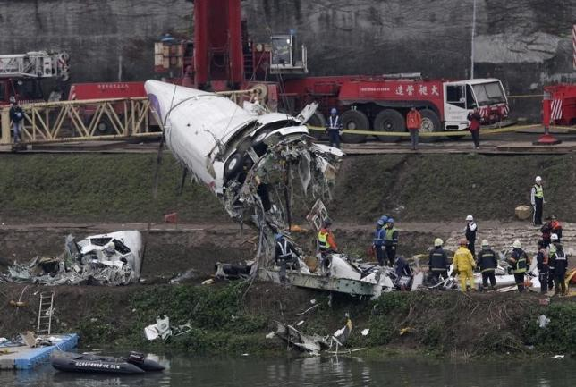 Emergency teams remove pieces of wreckage at the site of the crashed TransAsia Airways plane Flight GE235 in New Taipei City February 5, 2015.  REUTERS/Pichi Chuang/Files