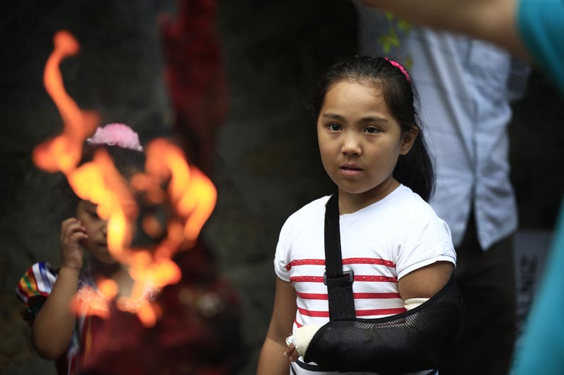 A young Uighur living in Turkey watches as protesters burn a Chinese flag outside China's consulate in Istanbul, Sunday, July 5, 2015, during a protest against alleged oppression by the Chinese government to Muslim Uighurs in far-western Xinjiang province. Photo: AP