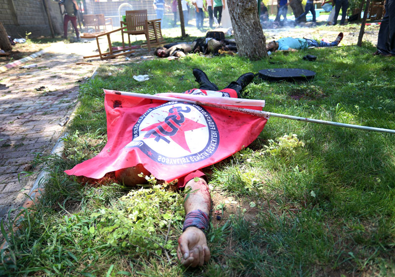Bodies lie on the ground with one being covered with a Federation of the Socialist Youth Associations flag, after an explosion, in the southeastern Turkish city of Suruc near the Syrian border, Turkey, Monday, July 20, 2015. An explosion Monday killed at least 10 people and injured scores of others in the southeastern Turkish city of Suruc near the Syrian border, state-run Turkish news agencies reported. The private Turkish DHA news agency said at least 50 people had been hospitalized in the midday explosion. There was no immediate claim of responsibility for the blast. Photo: AP