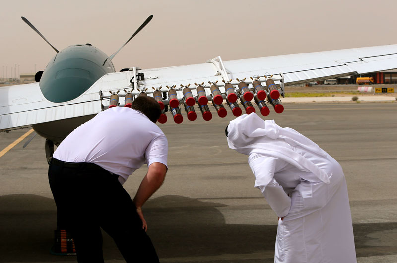 A pilot and a United Arab Emirates (UAE) official from the national center for meteorology and seismology check salt flares attached to a twin-propeller Beechcraft plane at al-Ain airport on April 23, 2015, that are fired into a promising cloud to increase condensation and hopefully trigger rainfall. Photo: AFP