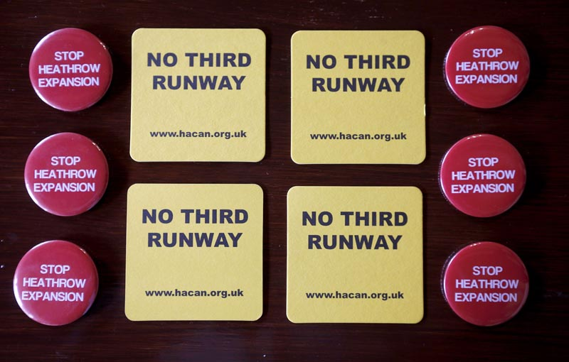 Badges and beer mats, protesting at the proposed expansion of Heathrow airport, are seen inside a pub in the village of Harmondsworth, adjacent to the airport in London, Britain July 1, 2015. Photo: Reuters