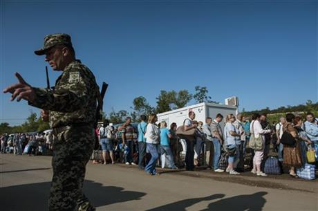 A Ukrainian army officer tries to handle residents of the Donetsk and Luhansk regions as they wait to cross a Ukrainian government forces' checkpoint at the road from Horlivka to Artemivsk to leave the territory controlled by Russia-backed separatists for Ukrainian territory near Artemivsk, Donetsk region, eastern Ukraine, Friday, July 17, 2015. AP