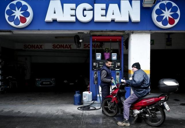 A man (right) refuels his motorcycle at an Aegean Oil gas station in Athens February 10, 2015.  Photo: Reuters