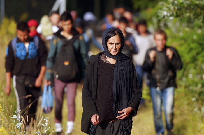 Migrants from Afghanistan walk after they crossed the border from Serbia to Hungary, near the village of Asotthalom, Hungary, on June 29, 2015. Photo: Reuters