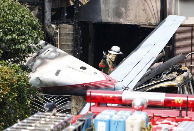 The tail section of a crashed light plane and burning house are seen after the plane went down in a residential area and burst into flames, in Chofu, outskirt of Tokyo, July 26, 2015. REUTERS/Yuya Shino