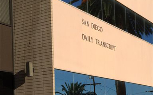 A person leaves the San Diego Daily Transcript building, Wednesday, July 22, 2015, in San Diego. The Daily Transcript said Wednesday it will publish its last edition Sept. 1, ending a nearly 130-year run in the newspaper business. The newspaper is no longer viable due to rising costs for health care and other expenses and an uncertain future for the industry, Publisher Robert Loomis wrote in a note to readers. (AP Photo/Elliot Spagat)