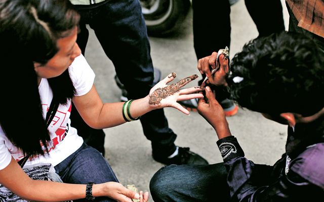 A man applying mehndi on the hand of a girl, in New Road, Kathmandu, on Thursday. Photo: THT